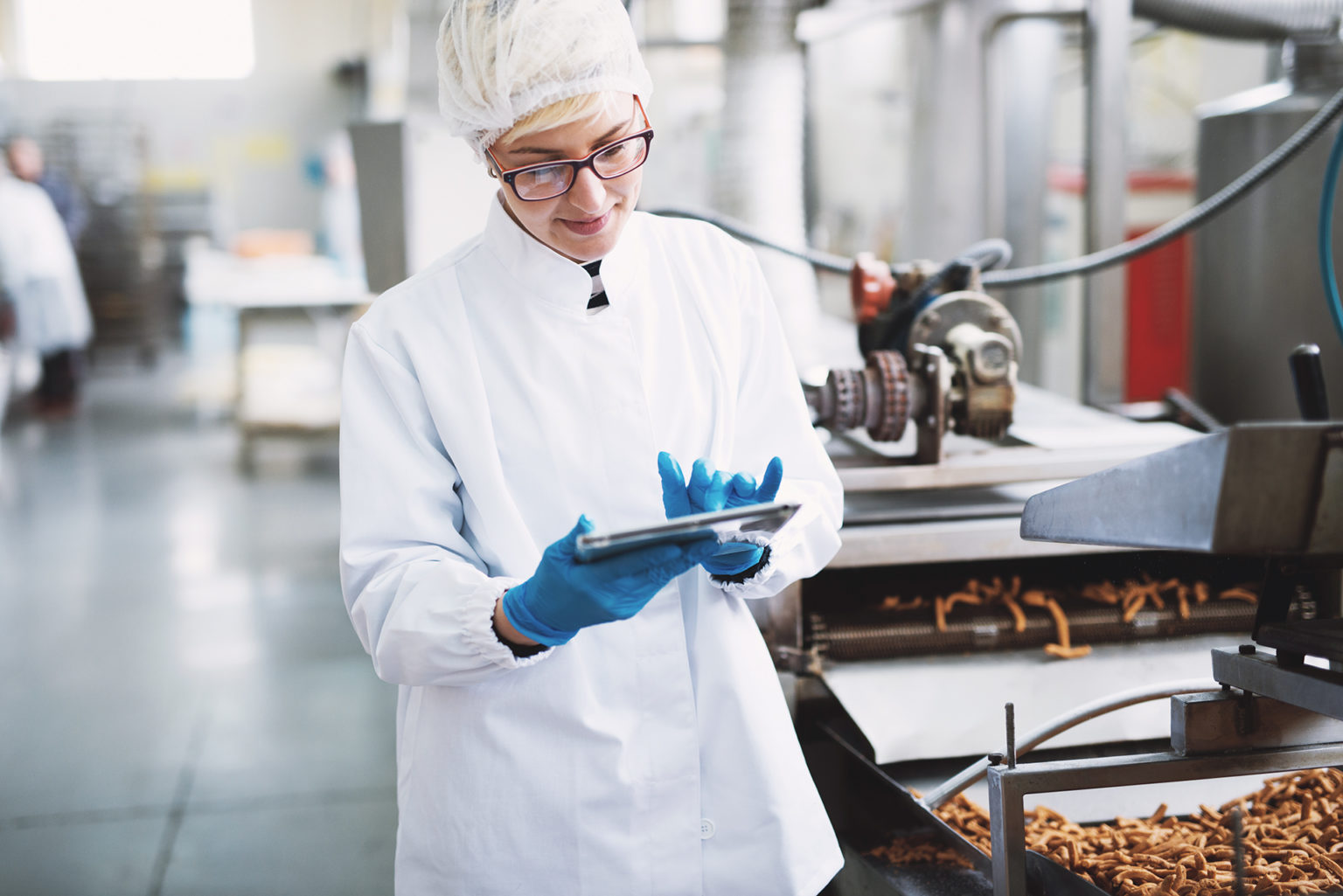 Young female worker in sterile clothes is checking quality of products in food factory.