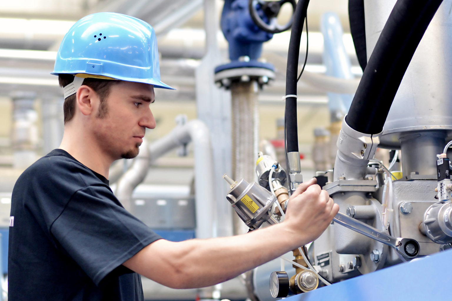 operator repairs a machine in an industrial plant with tools - pneumatics and hydraulics